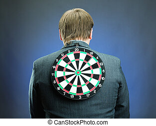 Businessman with darts board on his back isolated on gray