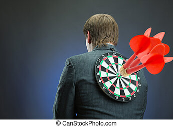 Businessman with darts board on his back with red darts