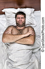 Unhappy man in bed with crossed hands - Top view of unhappy...