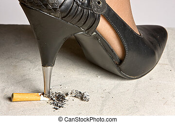 Crushing a cigarette - High-heeled stiletto shoe crushing a...