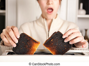 Burnt toast - Hands of a woman taking burnt toast out of a...