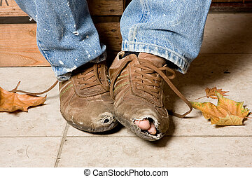 Battered shoes - Worn and battered shoes of a beggar in the...