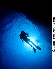 Scuba Diver Silhouette - A scuba diver is silhouetted by the...