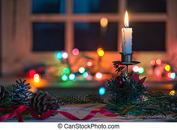 Candle with Christmas decoration, blurred light background