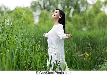 happy teenage girl with arms outstretched at park