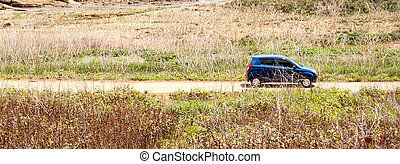 Car on country side road driving through
