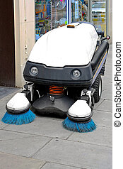 Street sweeper cleaning vehicle with revolving brushes