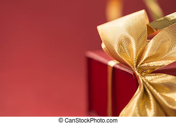 Gift box with golden bow on a red background