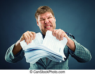 Angry man tear out paper - Angry man tearing out stack of...