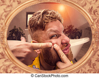 Adult man squeezes the pimple on his face looking in the...