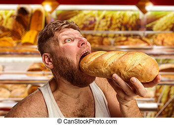 Man eating bread in the shop - Closeup of a man eating bread...