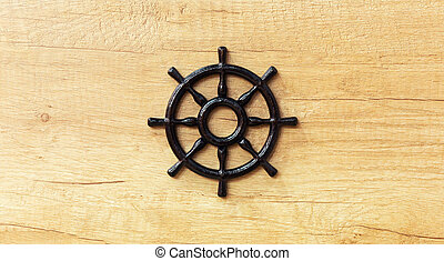 Beautiful ship steering wheel on wooden background