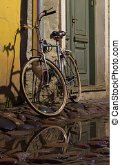 Vintage bike tied to the downpipe on cobbled street of old...