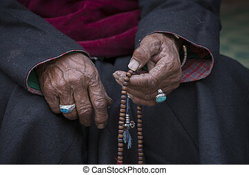 Old Tibetan woman holding buddhist rosary in Hemis...