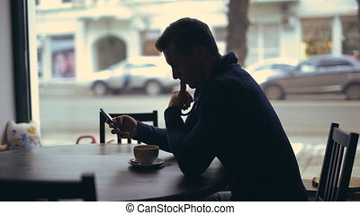 silhouette of handsome man with Smartphone in cafe -...