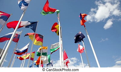 Different countries flags waving in blue sky - Sunny view at...