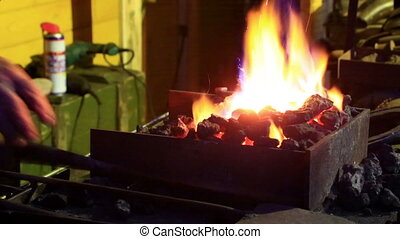 Bright flame over coals in a forge - Farrier lighting coals...