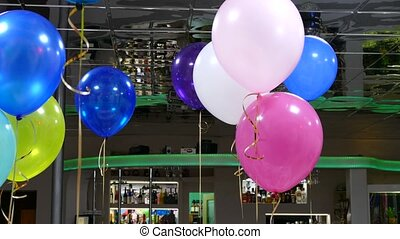 Helium balloons hang from the ceiling in the cafe...