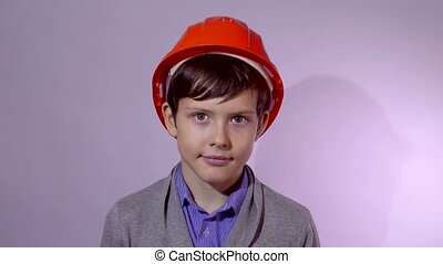 Teen boy builder in orange helmet studio portrait - Teen boy...