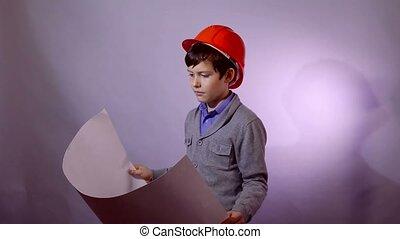 Teen boy builder in helmet holding building plan documents -...