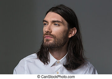 Serious man with beard and long hair looking away - Portrait...
