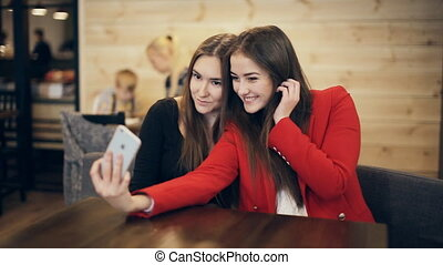 Two happy girlfriends taking selfie in cafe - Two happy...