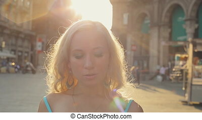 Attractive blonde wearing a dress walks in the center of...