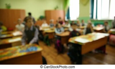 blurred background group of kids in classroom at school desk...