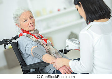 Checking an old lady's blood pressure