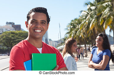Latin male student with friends in the city