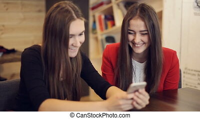 Two girlfriends with smartphone laugh in cafe - Two happy...