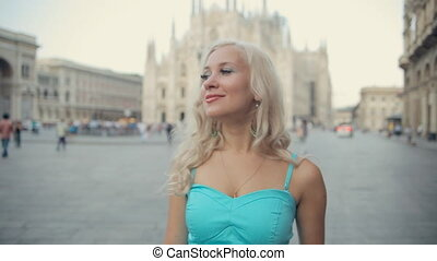 Happy girl walking down the street of Milan near the...