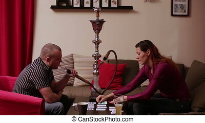 Woman and man smoking hookah and playing board game
