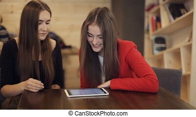 Two happy girlfriends with tablet smile in cafe - Two happy...