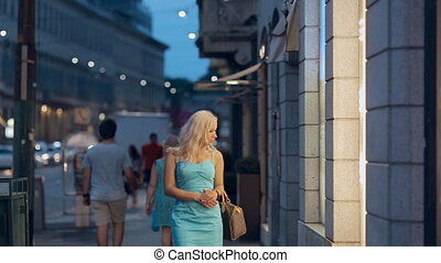 Girl looking on the storefronts of trendy shops in Milan