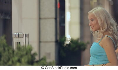 Stylish girl shopaholic looks in the windows of shops in...