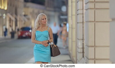 Shopaholic woman looking in the windows of boutiques while...