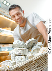Shop assistant with basket of cheeses