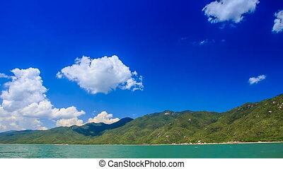 close view of green hilly island cloud shadows against blue...