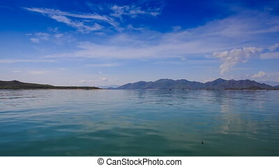 view of azure sea against distant islands blue sky fleecy...