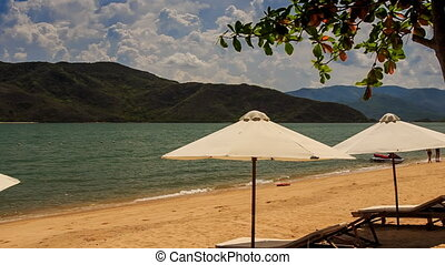white sunshade parasols on sand beach at azure sea - white...