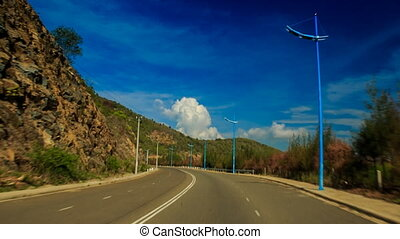 camera moves fast along road past hills tropical plants -...