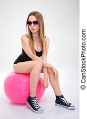 Modern style dancer posing on pink fitball - Modern style...