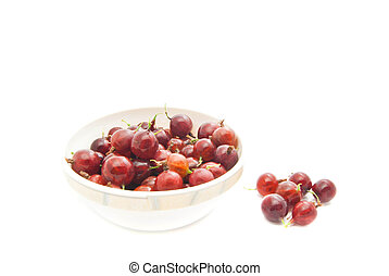 red gooseberries on a dish on white closeup