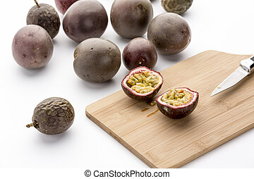 Freshly halved Passion Fruit On A Bamboo Board