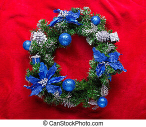 Christmas wreath with baubles on a red