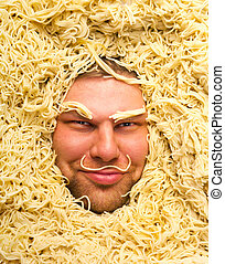 Man's face in pasta, closeup - Happy man's face in pasta,...