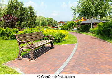 Bench in the local park and brick path to the houses