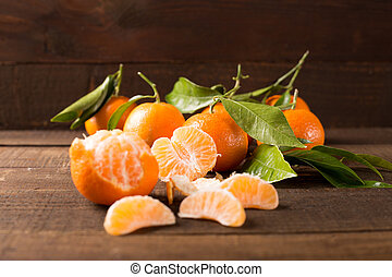 clementines - closeup of fresh clementines over dark wooden...