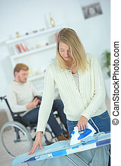 Woman ironing for her disabled boyfriend